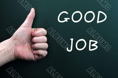 Thumb up with good job written on a blackboard