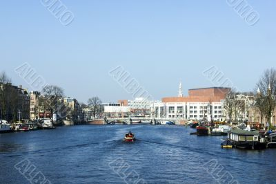 Amsterdam city in the Netherlans, boat in the river Amstel