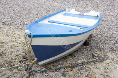 Blue and white boat on the shingle beach
