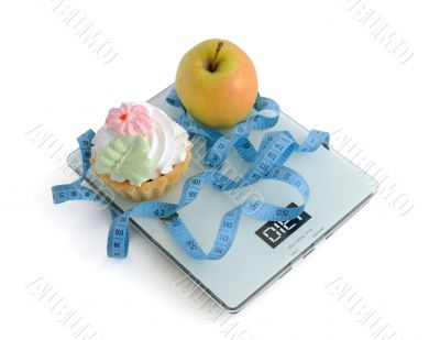 Cake and apple on scales measuring tape wrapped