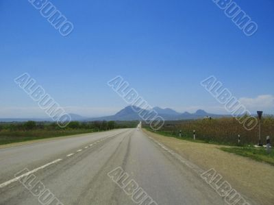 Wide highway and mountain. Clouds over and blue sky