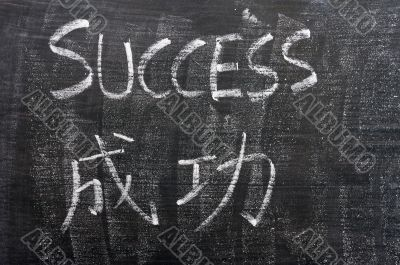 Success - word written on a blackboard with a Chinese translation