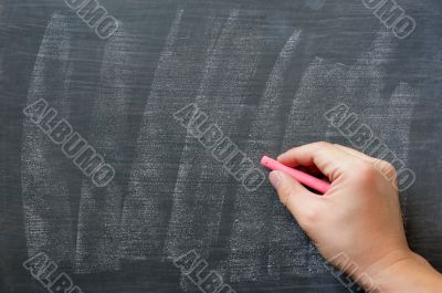 Hand writing on a smudged blank chalkboard with chalk