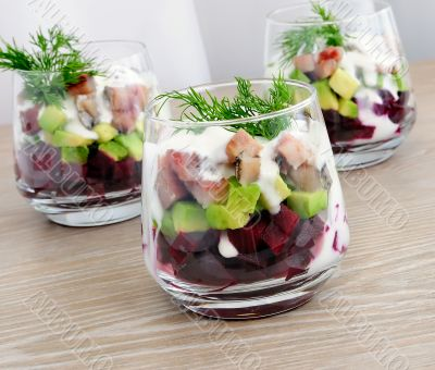 Appetizer in a glass of beet and herring with avocado