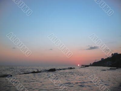 Round sun falling down over the Black sea