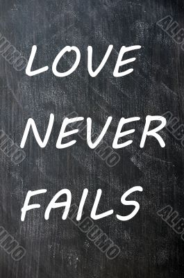 Love Never Fails written on a smudged chalkboard