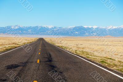 Empty freeway approaching mountains range