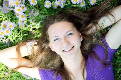 Teen girl laying in grass