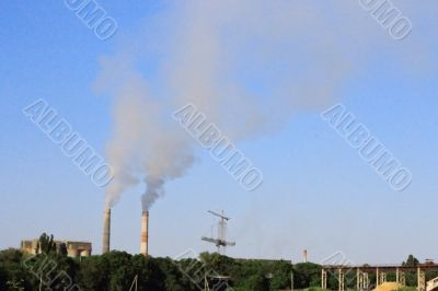 Smoke stacks of cement factory. Summertime landscape