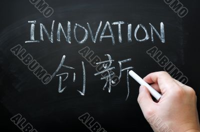Innovation - word written with white chalk in both English and Chinese
