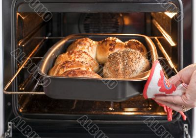 Baker`s hand with bread in oven