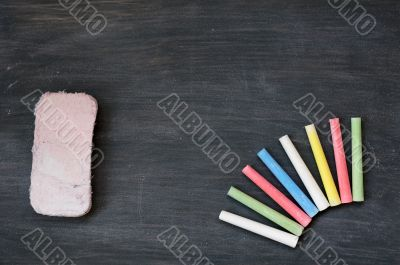 Colorful chalk and eraser on a blank smudged blackboard