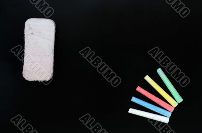 Colorful chalk and eraser on a blank blackboard