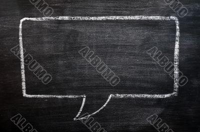 Blank speech bubble drawn on a smudged blackboard