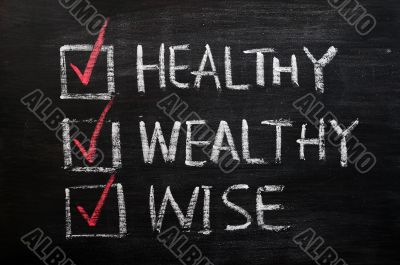 Being healthy, wealthy and wise written with chalk on a blackboard