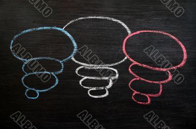 Blank speech bubbles drawn in chalk on a blackboard