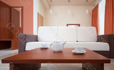 Teapot and cups on the background of the sofa