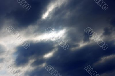 Blue sky and heavy clouds and the sun behind