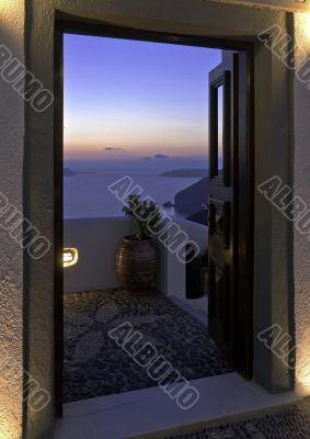 Santorini Caldera twilight view trough the open door
