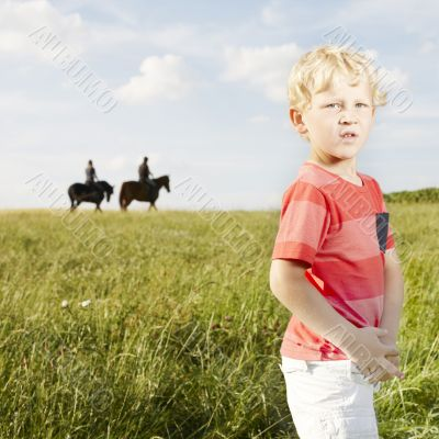 Young blonde boy standing in a grassy field