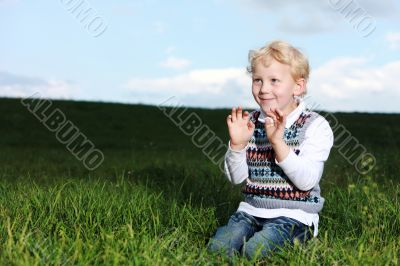 Impish little boy kneeling in green field
