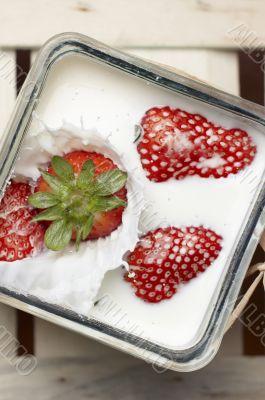 Strawberry falling and splashing into milk
