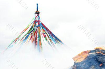 Tibetan prayer flags and mani rock in the smoke