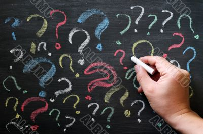 Question marks on chalkboard. Decision, confusion, FAQ or other concept. Hand writing with chalk on school black board.