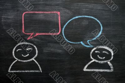 Blank speech bubbles with cartoon figures drawn on a blackboard background