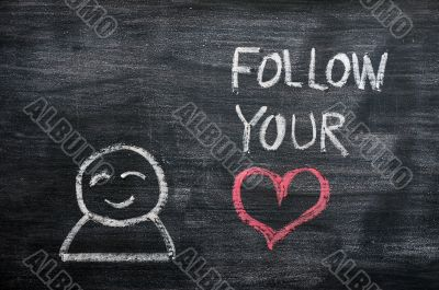 Speech bubble with a cartoon figure and the phrase `Follow your heart` drawn on a blackboard background