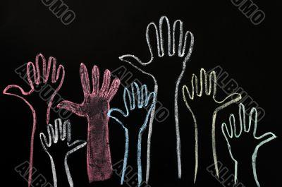 Happy volunteering hands on a blackboard background