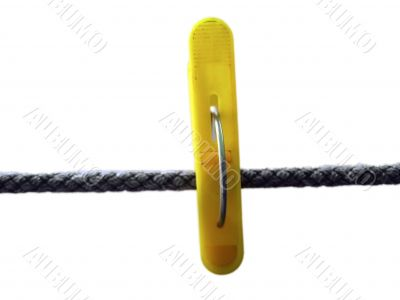Yellow clothes peg and string on the white background isolated