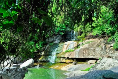 A small waterfall with rocks and green trees