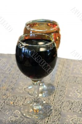 Two glasses on the table with a white tablecloth isolated on the