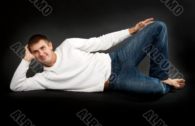 man in a white sweater lying