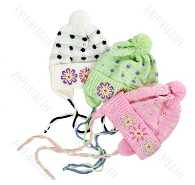 three colored children`s knitted hat with a flower pattern