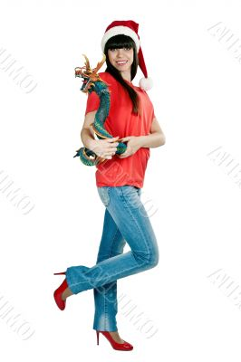 Girl in Santa hat with a decorative wooden dragon