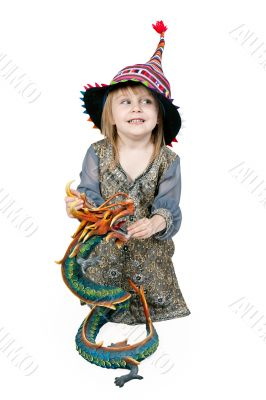 Little girl sitting on the floor with a decorative dragon