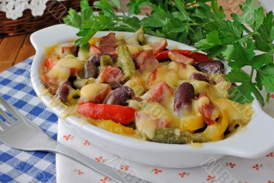 Beans with ham and vegetables, baked with cheese