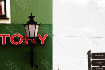 Nostalgic lamp in front of a green house facade
