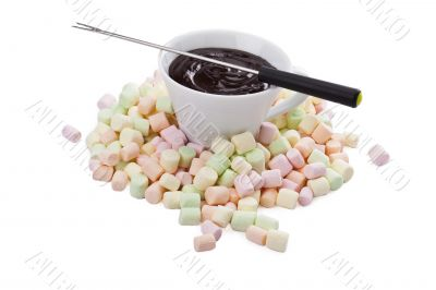 cup of melted chocolate in pile of colorful marshmallow