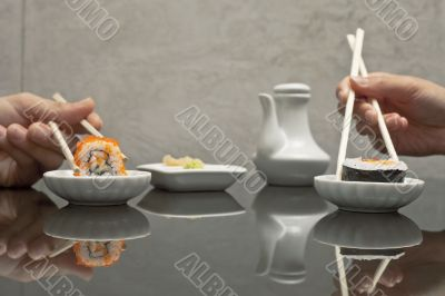 hands holding sushi with chopsticks at restaurant