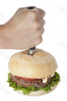 hand stabbing a hamburger