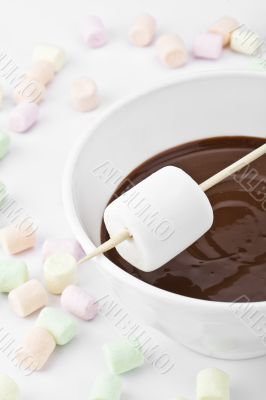 white marshmallow on stick above the melted chocolate bowl