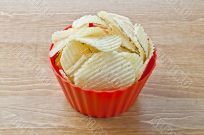 crispy potato chips in red bowl