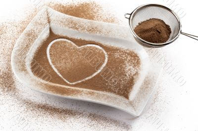 strainer with cocoa while heart shape on a white container