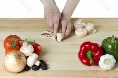 female hand slicing a mushroom for pizza