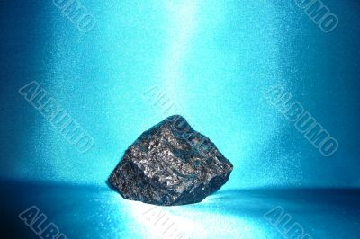 Dark gray shiny stone on a blue background.