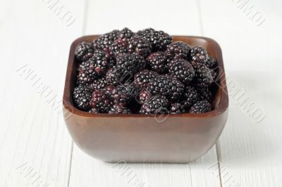 pile of blackberries on wooden bowl