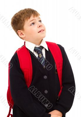 School boy standing and looking up with his backpack.